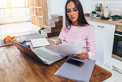 Woman looking at documents at a laptop